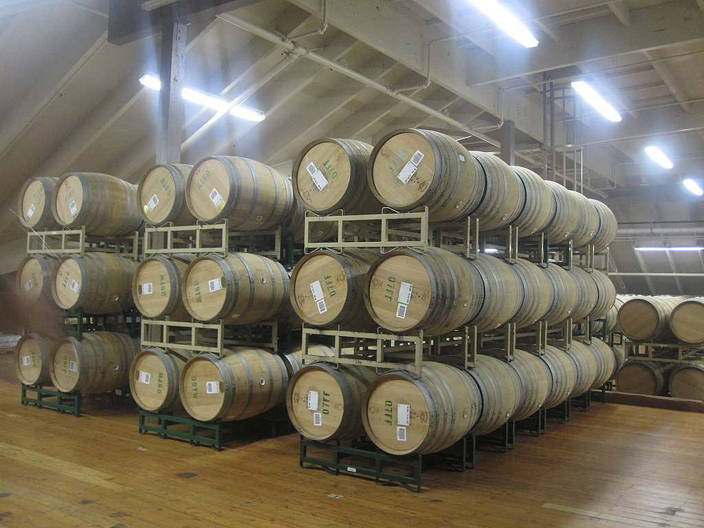 There are hundreds of barrels housed in the facility. The floor on the top level is the building's original flooring and can only hold the weight of three stacked barrels. Barrels that are labeled in green contain white wine and barrels that are marked in red house red wine.