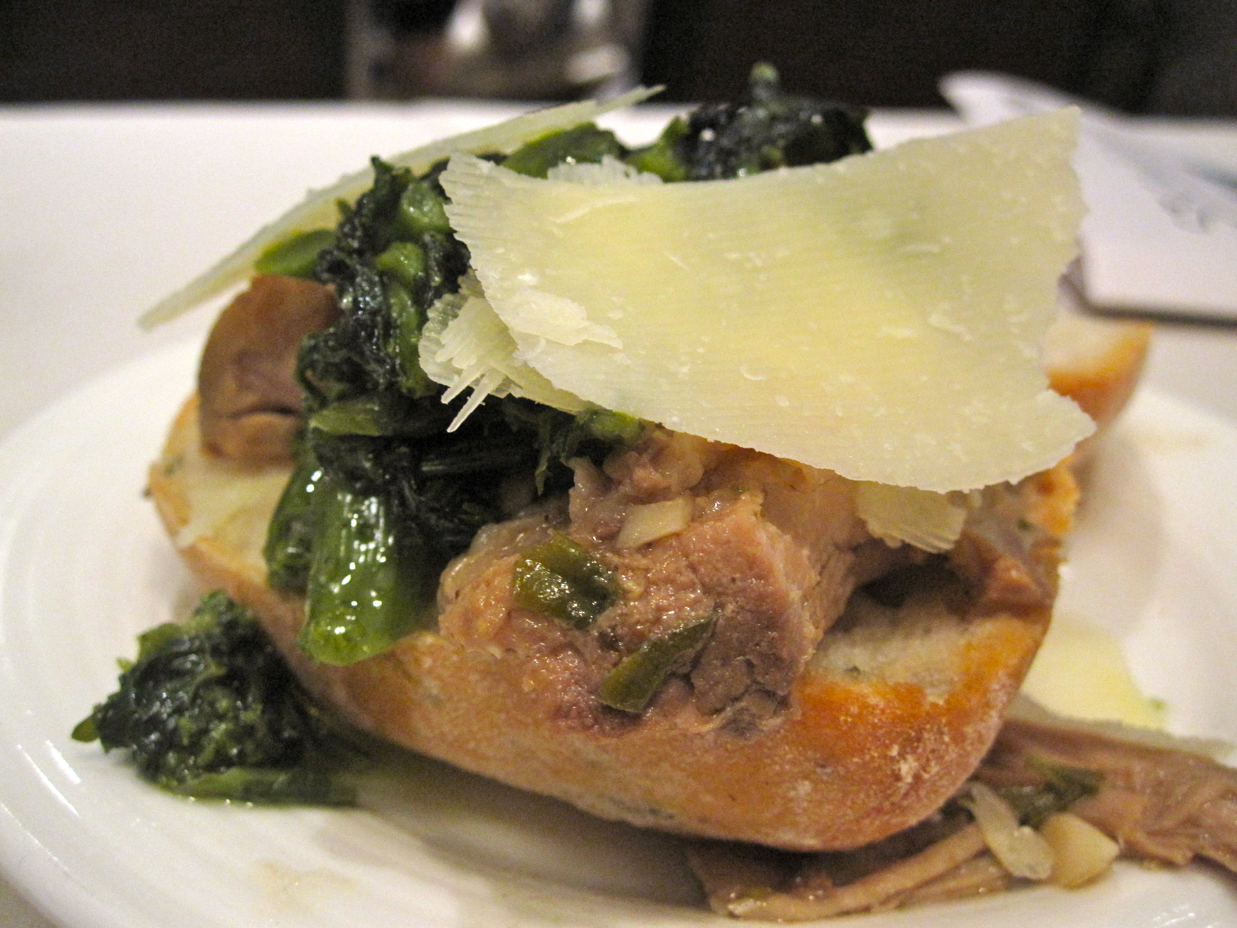 The porchetta was served on a sandwich roll with braised broccoli rabe and shaved parmesan cheese.