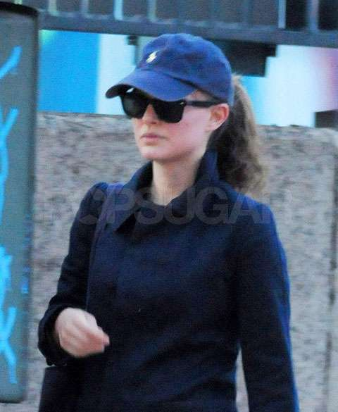 Natalie sported a cute baseball hat and sunglasses.