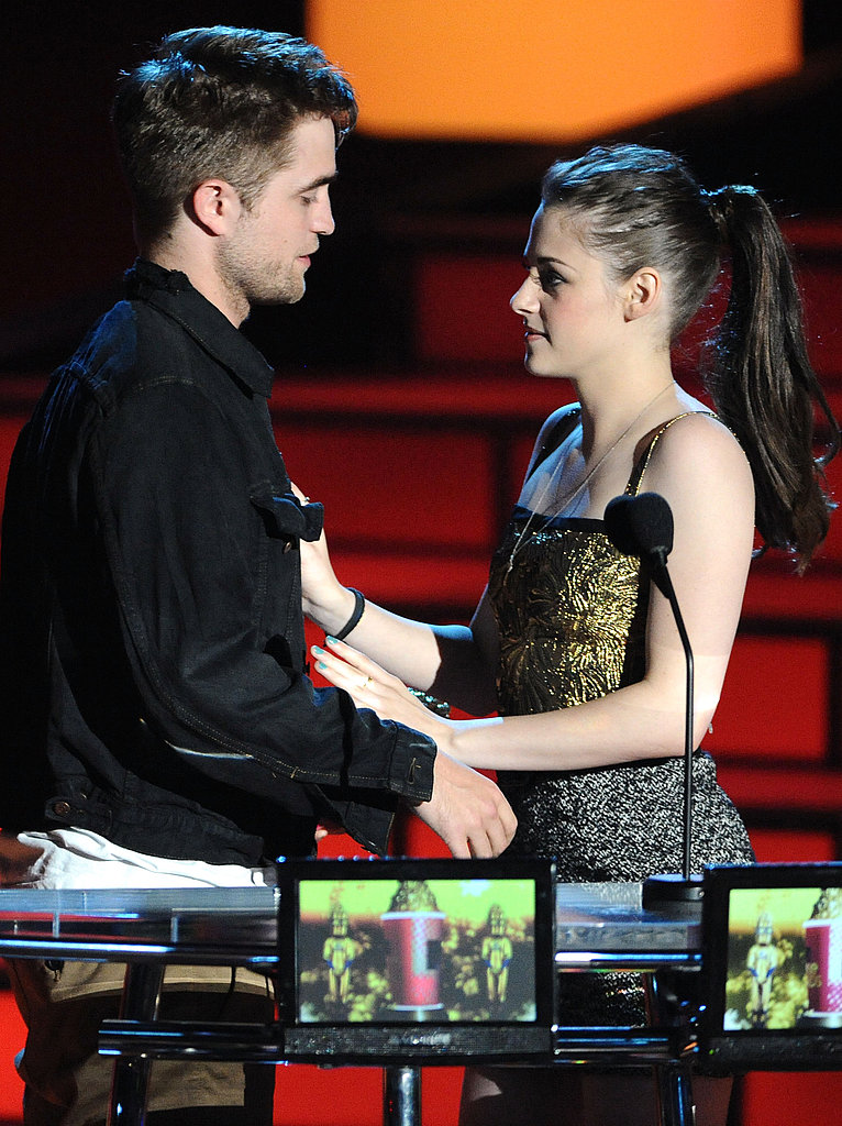 Robert Pattinson and Kristen Stewart got cosy while staging a kiss at the 2010 MTV Movie Awards.