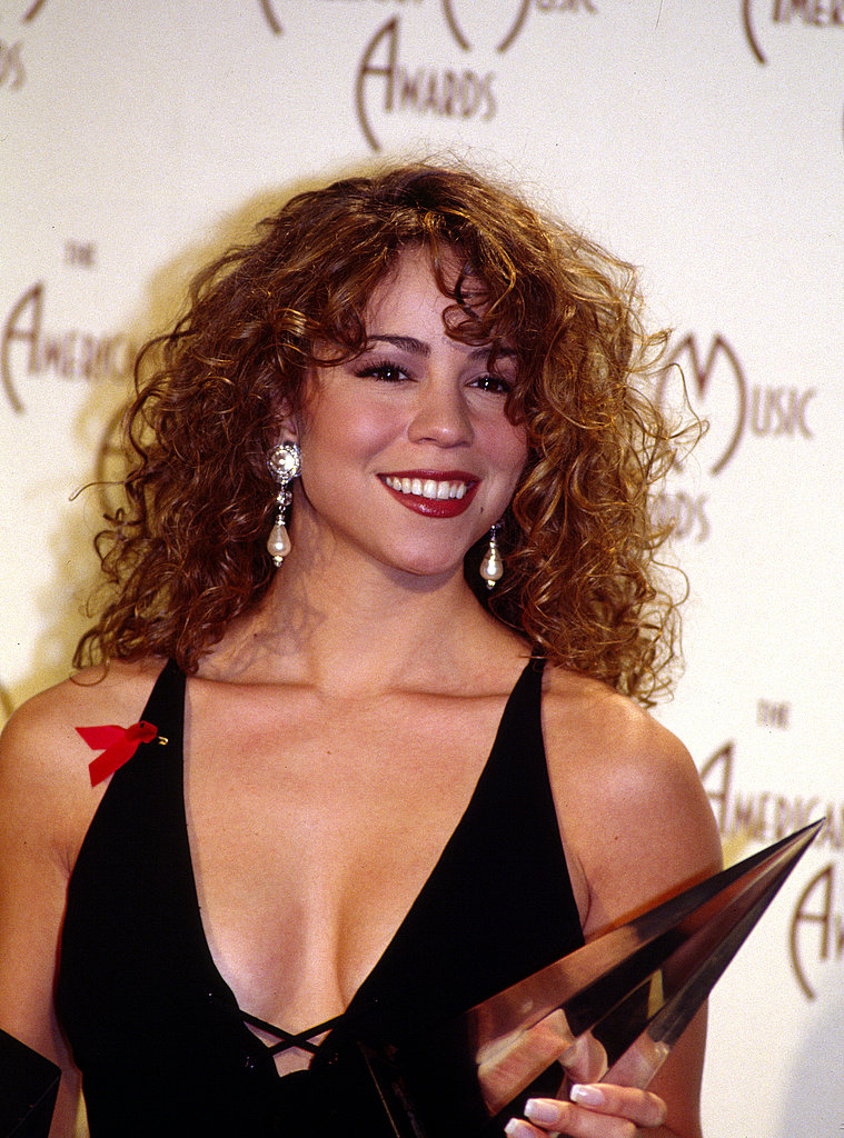 A curly-haired Mariah Carey posed in the press room with her awards in 1993.
