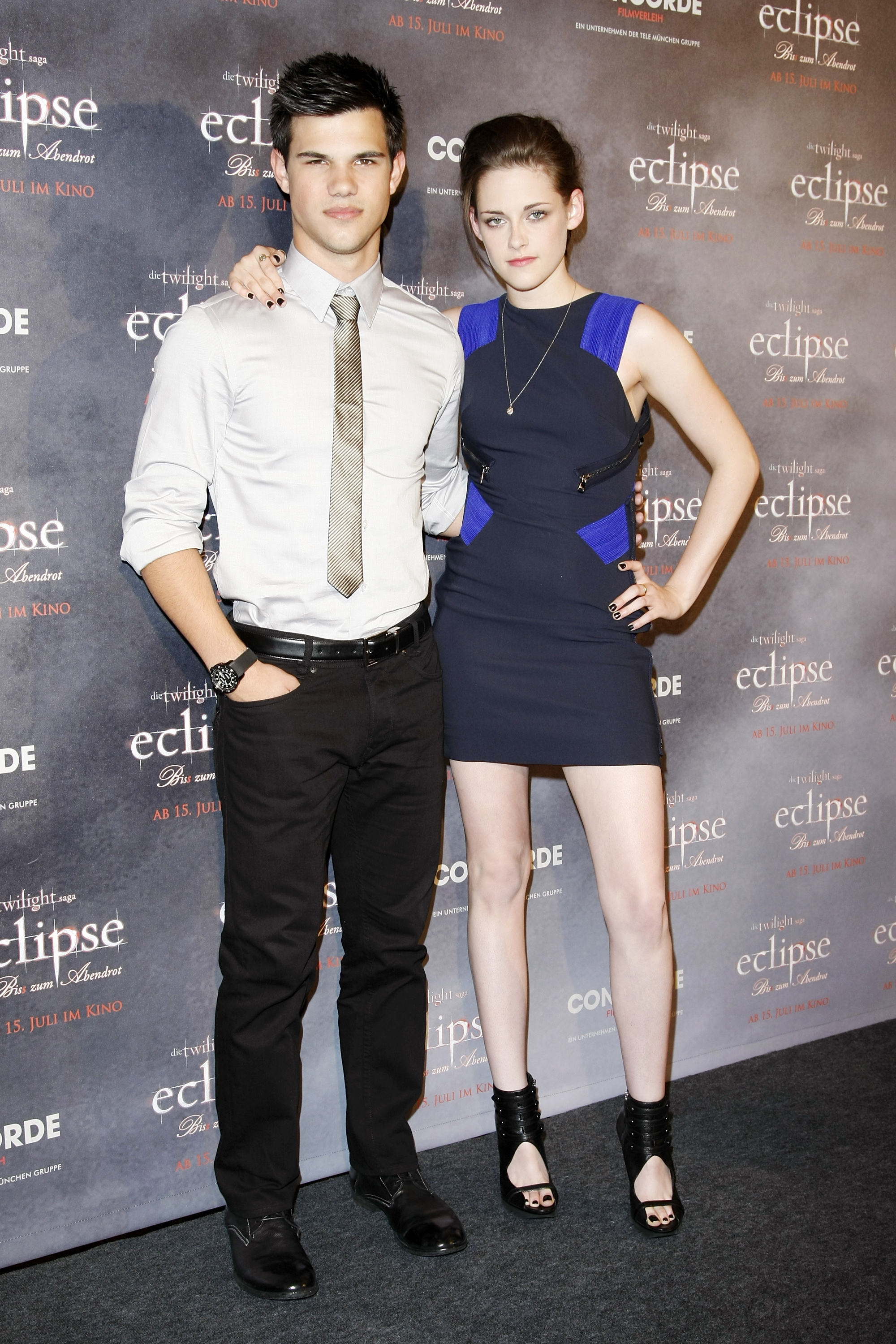 Kristen rocked a hot Versace number and hung onto Taylor Lautner to promot