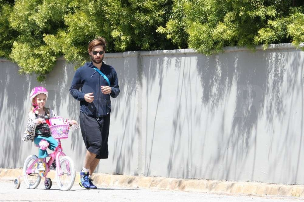 Tobey Maguire jogged alongside Ruby Maguire and her bike.