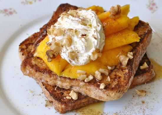Wheat bread French toast topped with sliced fresh mangoes, honey, whipped cream and chopped walnuts