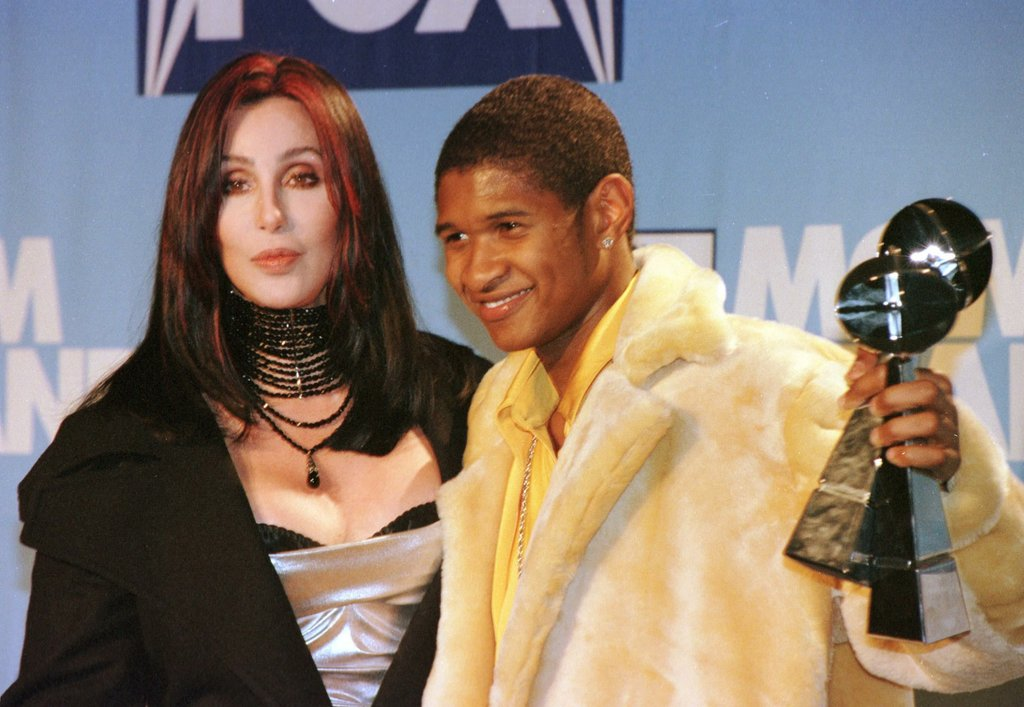 Usher showed off his artist of the year Billboard award next to Cher in 1998.