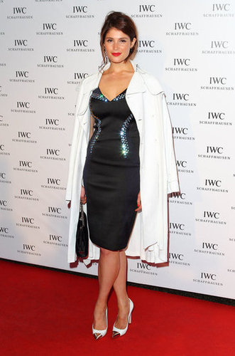 Gemma Arterton topped her frock with a chic white coat.