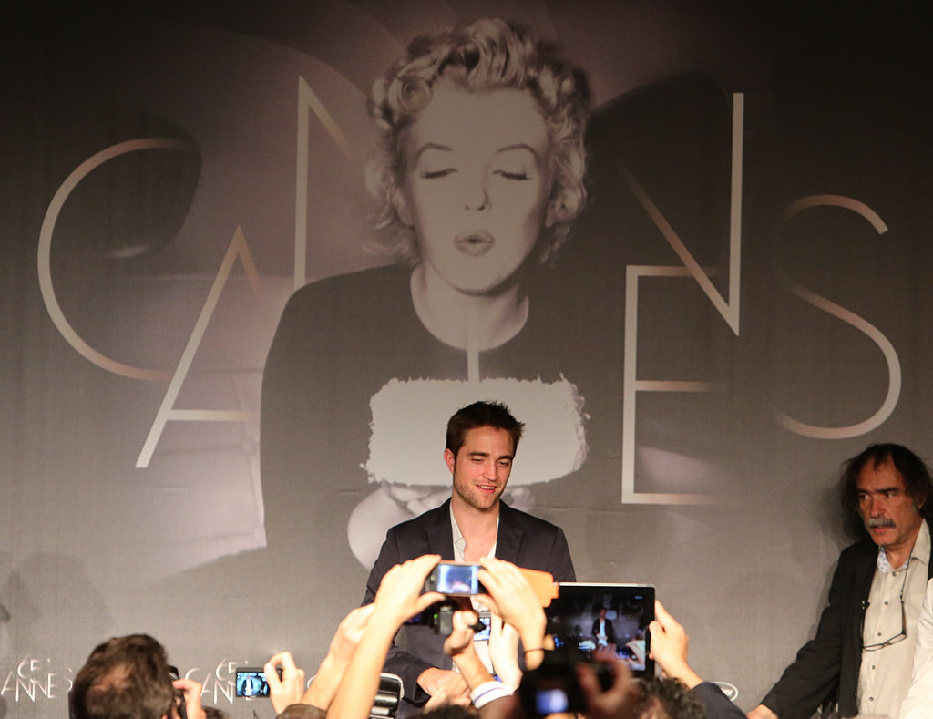 Robert Pattinson posed infront of a Marilyn Monroe backdrop at the Cosmopolis photocall in Cannes.