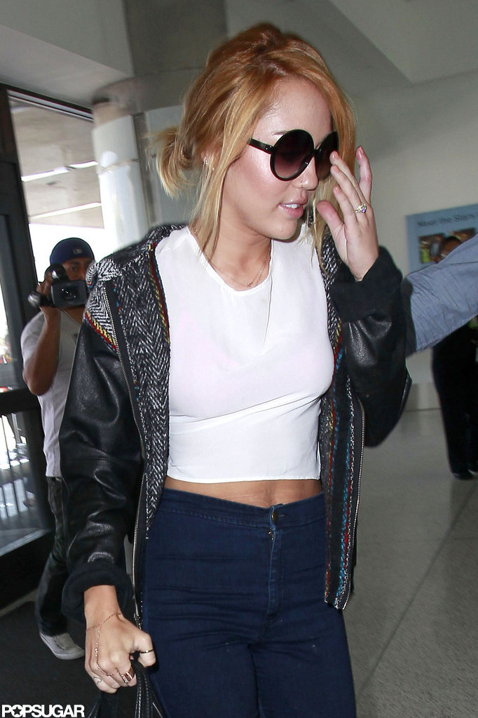 Miley Cyrus showed off her tummy in a white tube top wearing her engagement ring at LAX.