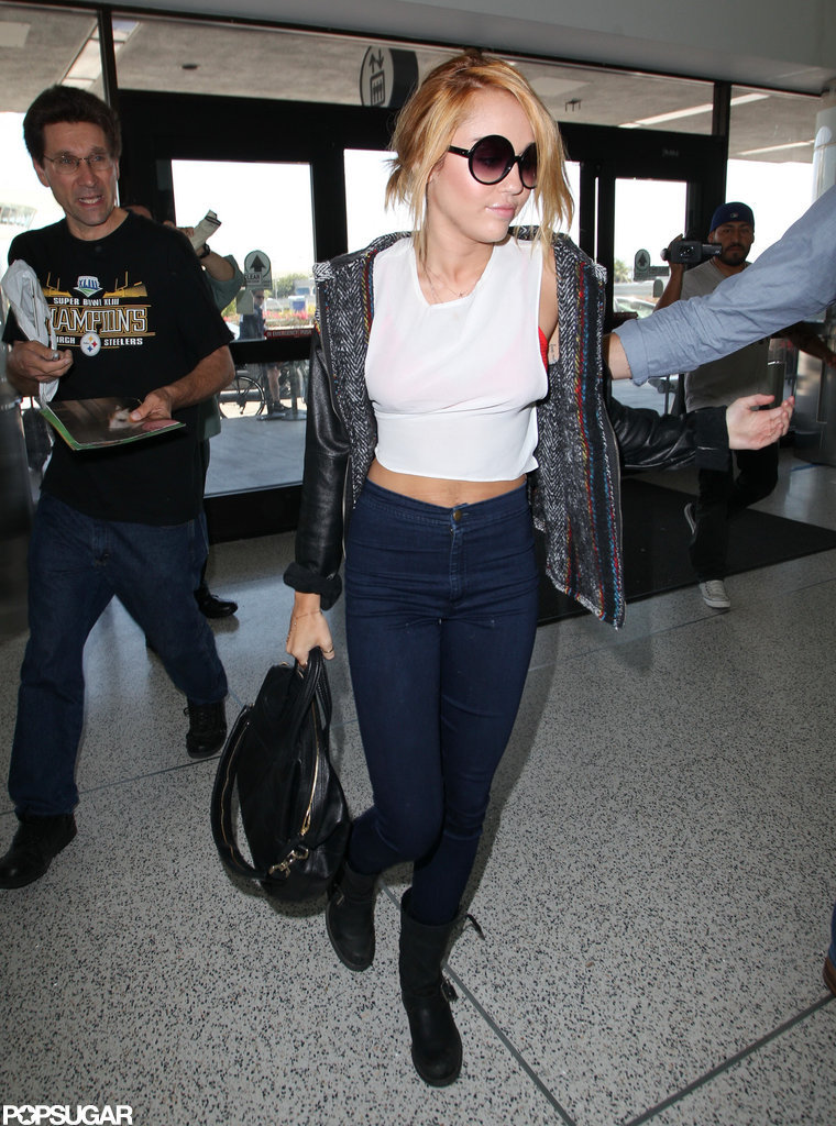 Miley Cyrus showed off her tummy in a cropped white shirt boarding a plane at LAX.