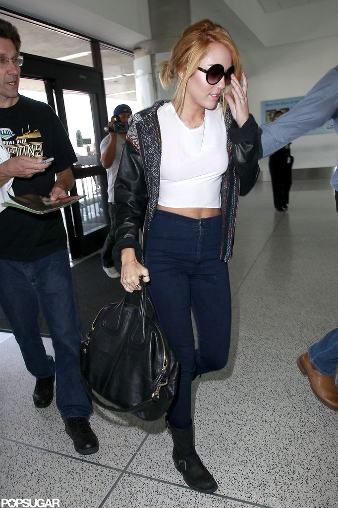 Miley Cyrus wore sunglasses and a white crop top to LAX.