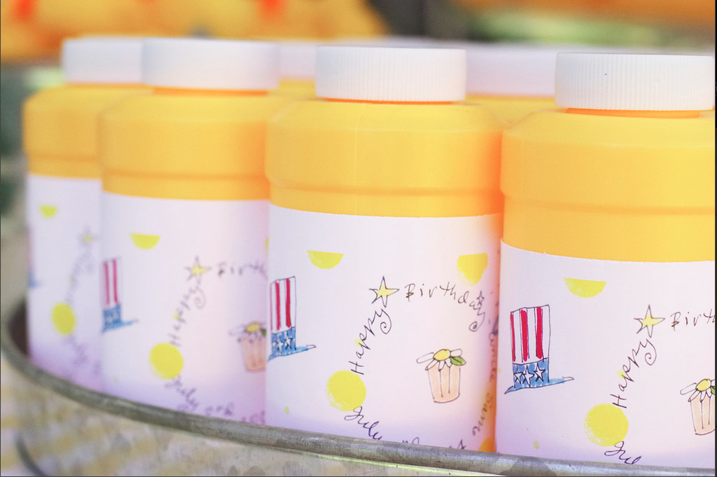 It wouldn't be an outdoor party — birthday, shower, or otherwise — without some bubbles! Darcy added her own label to the yellow bottles to tie them in with her theme. Source: Donna Newman Photography