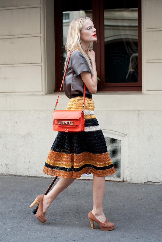 Not overly complicated, but the textural intrigue on her striped a-line skirt and a pop of cherry-red on her bag, takes this look from casual to covetable.