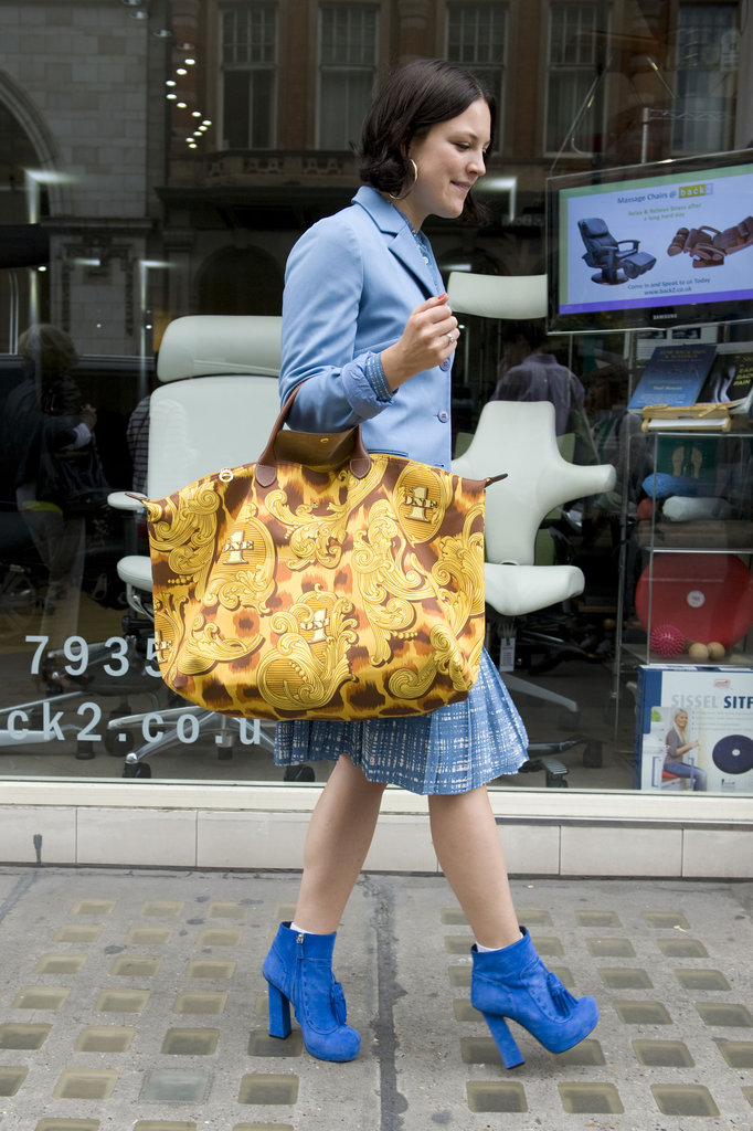 What catches your eye more — her oversize printed Longchamp tote or electric-blue tasseled ankle boots?