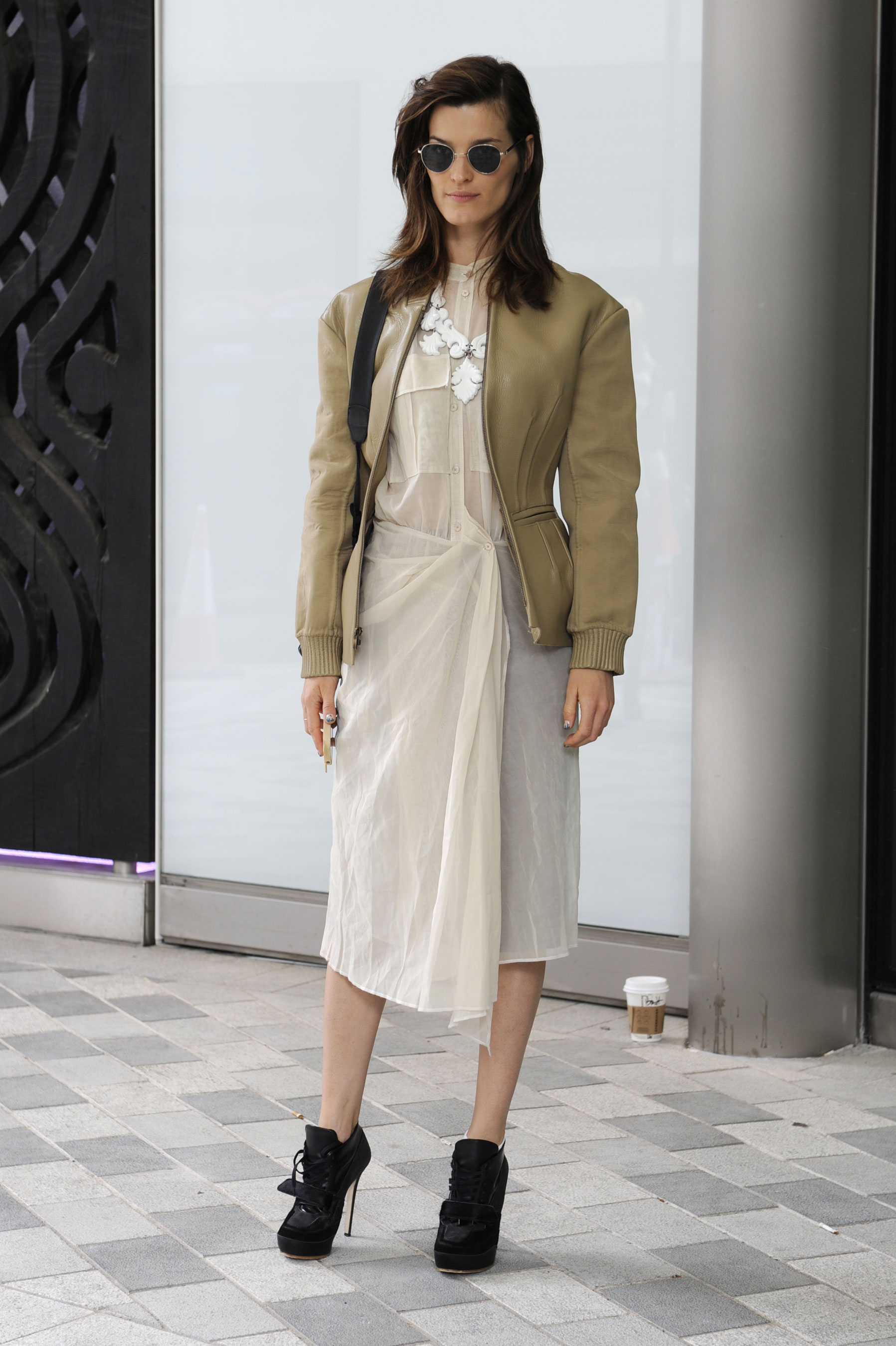 Hanneli Mustaparta toughened up a breezy, white chiffon dress with a military-style jacket and black, athletic-style booties.