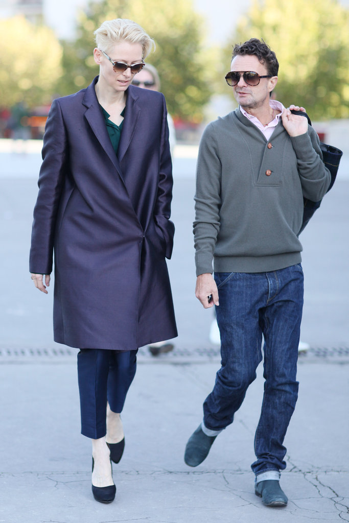 Tilda Swinton balanced tailored trousers with an architectural, jewel-toned coat.
