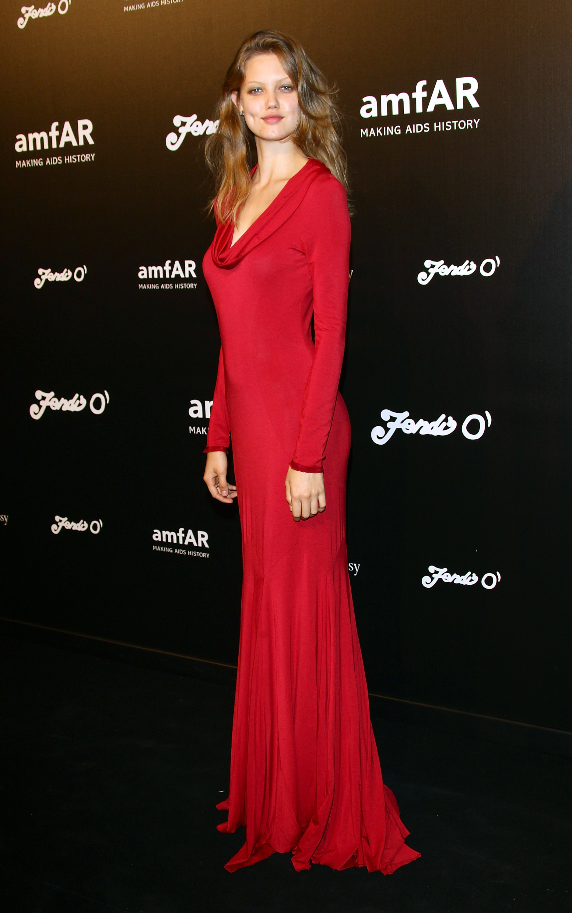 Lindsey Wixson opted for a  dramatic red gown with a draped neckline at the amfAR Milano fete.