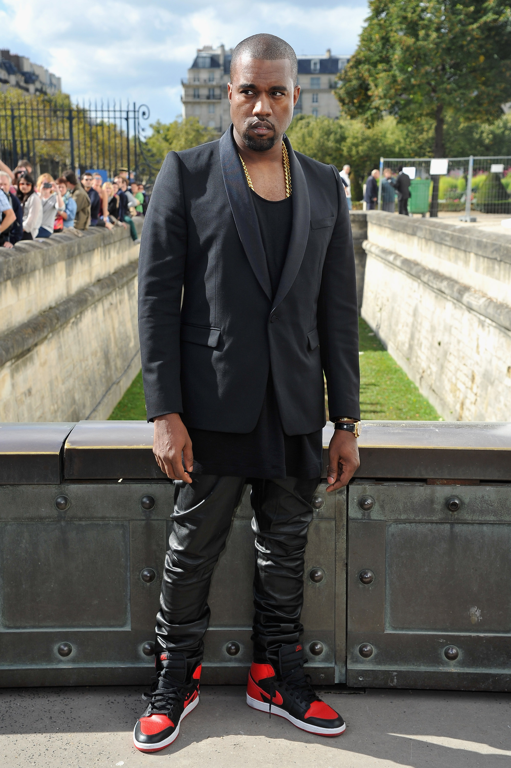 Although he isn't showing his own collection this season, Kanye West turned up to the Christian Dior show in red Nike Dunks, a sleek black blazer, and black leather pants.