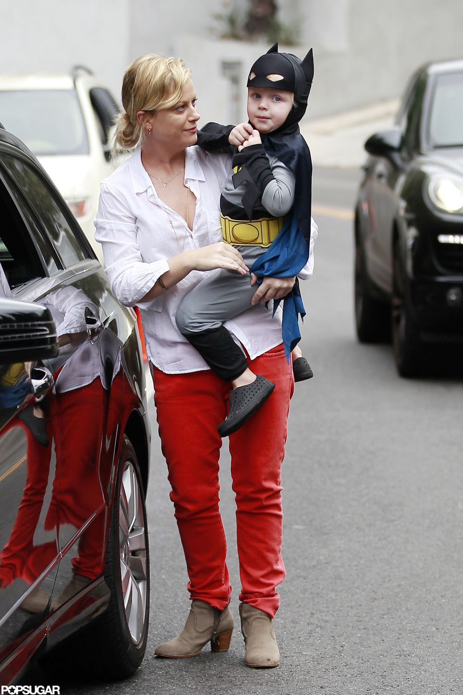 Amy Poehler carried her son, Archie Arnett, dressed as Batman to a costume birthday party in LA.