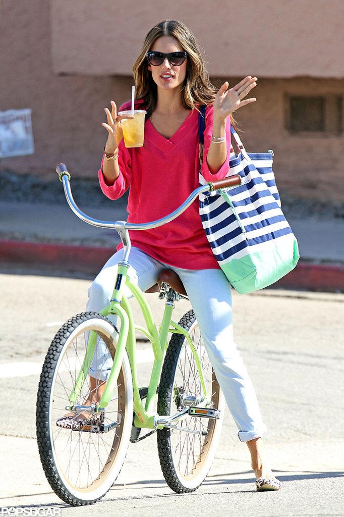 Alessandra Ambrosio balanced a drink and a bag.