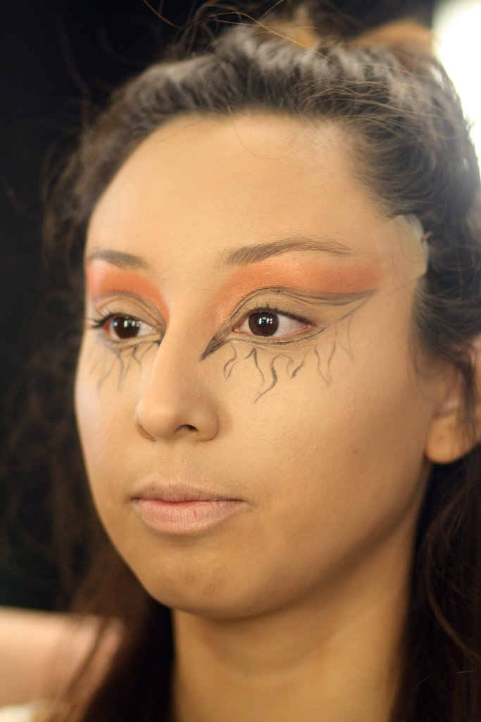 Next, Zizzo began to add color. Under the eyebrows, she applied Pro Pigment in Acid Orange for a frosty texture. The matte base of Devil blush ($17), applied along the crease of the eyelid, provided depth. Finally, to further highlight the eyes, Zizzo applied Ricepaper ($15) eye shadow under Lisette's brows.