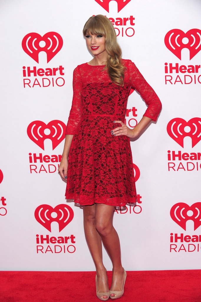 Taylor Swift's bright red French Connection lace dress may just be the perfect solution to your holiday dressing woes.