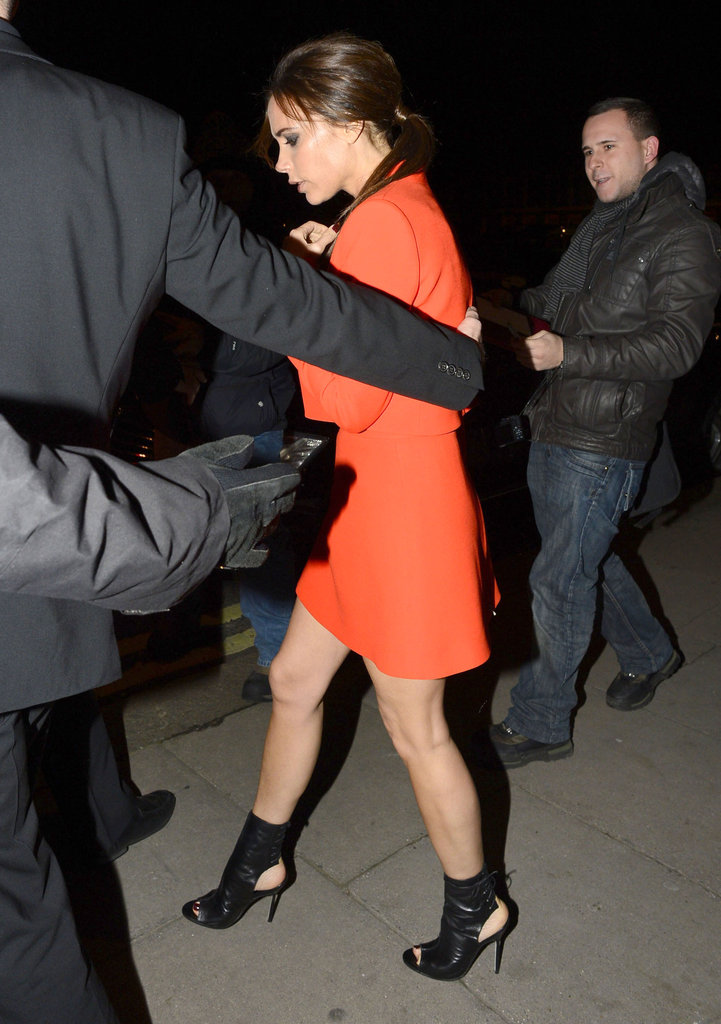 Victoria Beckham wore a bright orange ensemble to step out for the launch of a new Valentino exhibit in London.