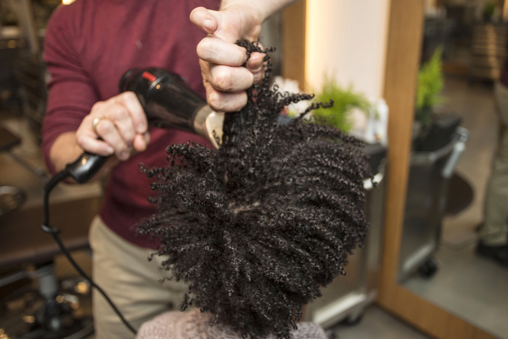 The next step to getting the big hair of your natural dreams is to stretch it with a blow dryer. Focus the heat at your roots while pulling hair from the midshaft. In order to prevent frizz, however, try to avoid combing hair with your fingers.