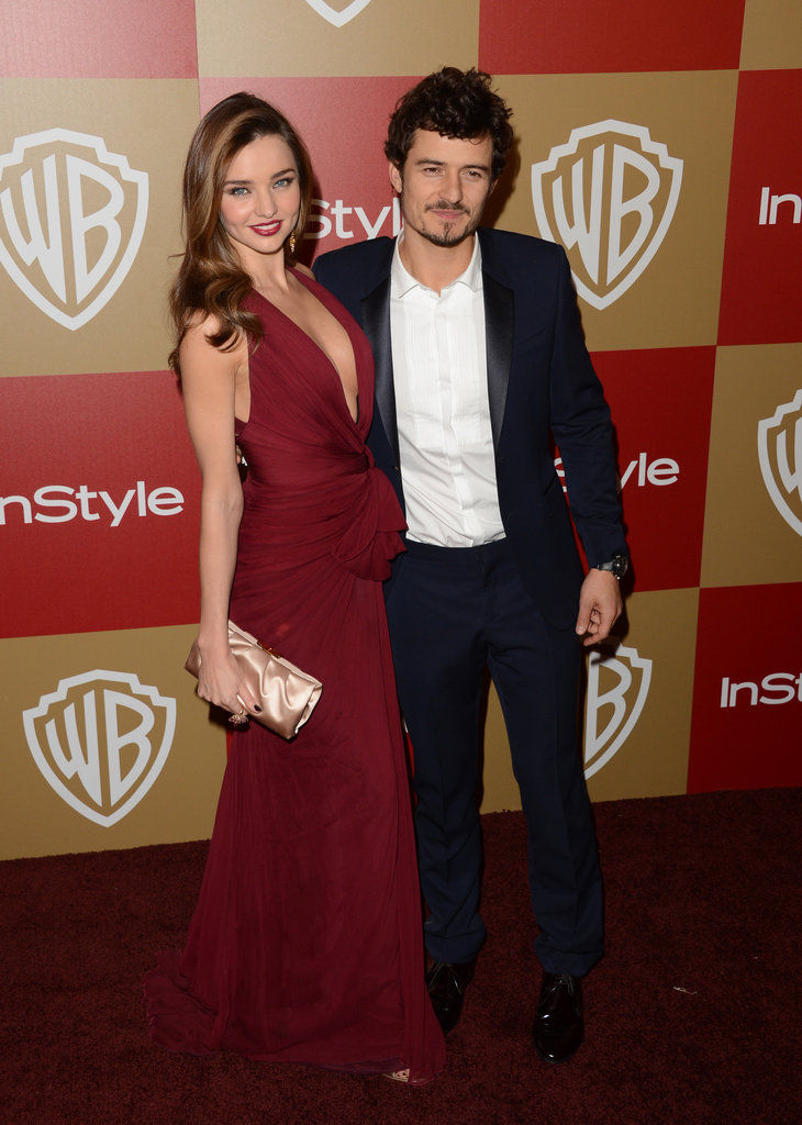 Miranda Kerr and Orlando Bloom put their arms around each other.
