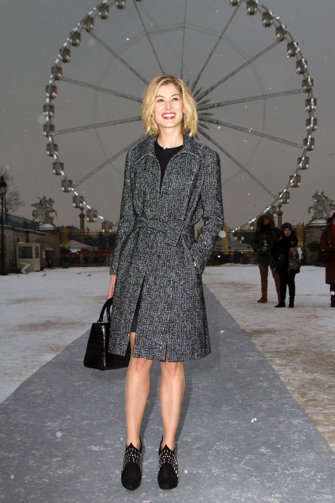 Rosamund Pike donned a little black dress with studded booties, then finished off her Parisienne look with a tweed coat and a black Dior satchel.