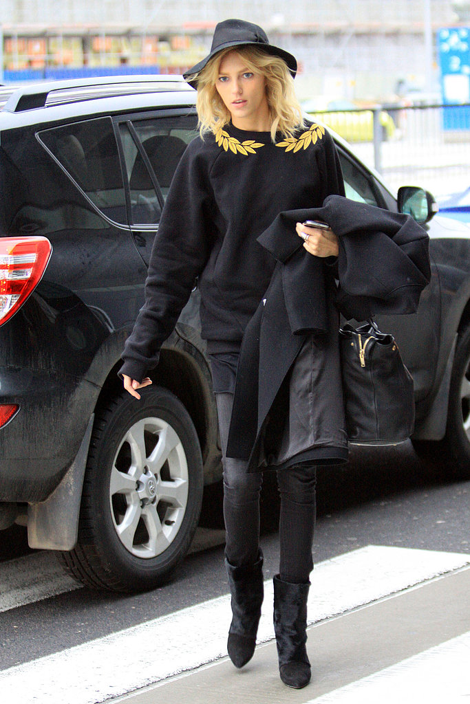 Anja Rubik arrived in Poland wearing a black sweater — the gold leaf detailing was the perfect pop of color — black leather pants, black boots, and a black hat. She held onto a black coat and a black leather bag.