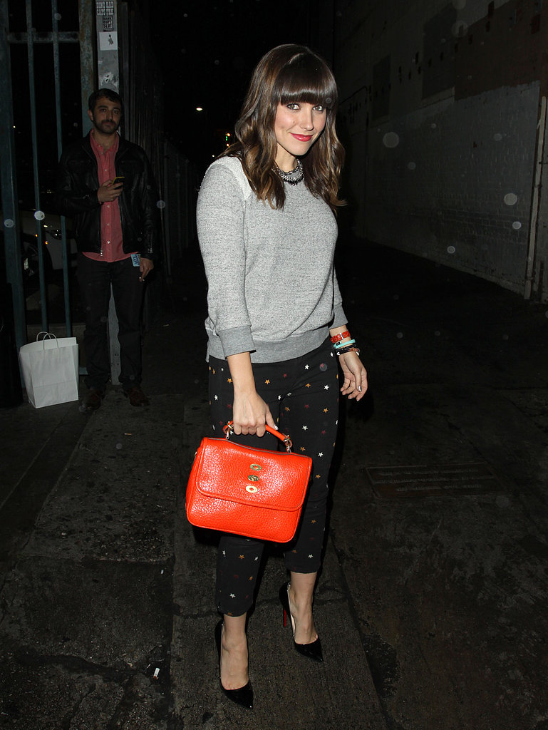 Sophia Bush punched up her nighttime style via these Etoile Isabel Marant star-print jeans ($355), a 194t sweatshirt, and a structured orange bag.