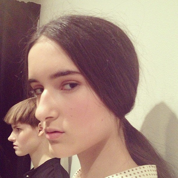 The hair at Suno was swept back into a classic low ponytail that covered the ears.