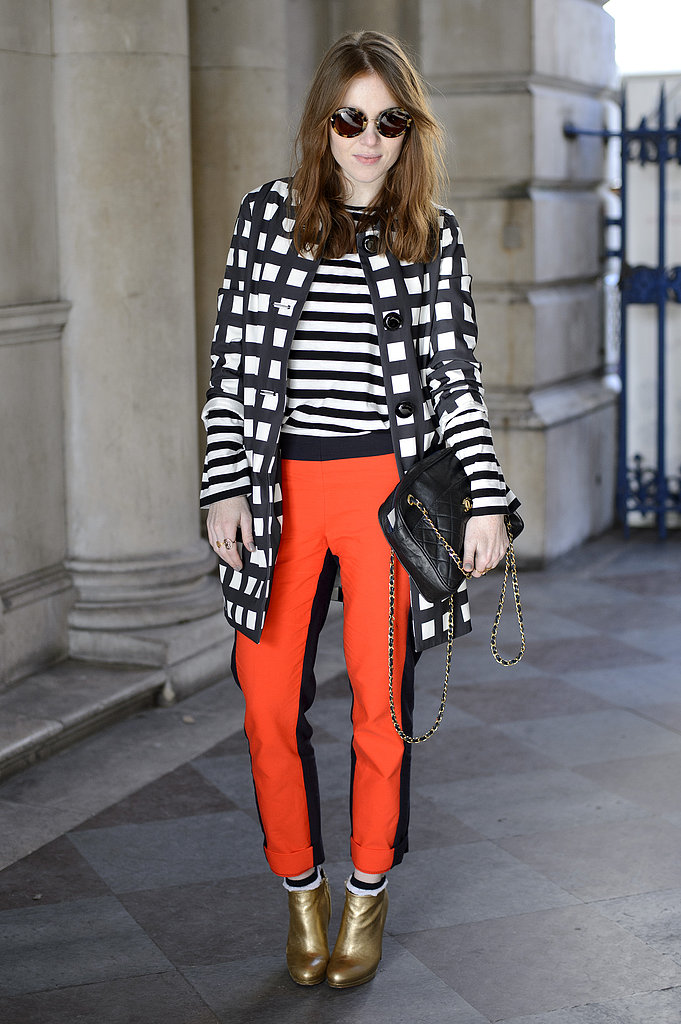 A windowpane-patterned coat added print-on-print play off her stripes and bright pants.