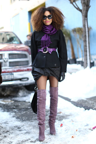 This show-goer flaunted her mile-log stems in over-the-knee boots and furthered her outfit flair with pops of purple.