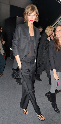 Karlie Kloss strolled Lincoln Center in a black tuxedo suit, sheer black tee, and strappy sandals.