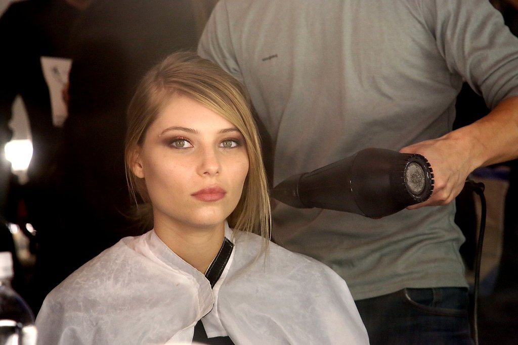 """The part is natural and imperfect with a bit of a broken side bang. If you have trouble getting the perfect blowout at home using a round brush, then take this shortcut from Moodie. """"Use a paddle brush like a Mason Pearson, which actually isn't completely flat because the padding on it makes it curved,"""" he explained. Also, take advantage of a straightening iron's curvature on the ends. """"Go through with a flat iron so you make a slight bend, so it feels blow-dried not ironed,"""" he added."""