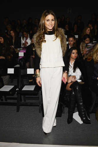 Olivia Palermo tossed a fur vest over her colorblock sweater and wide-leg white trousers at Rachel Zoe.