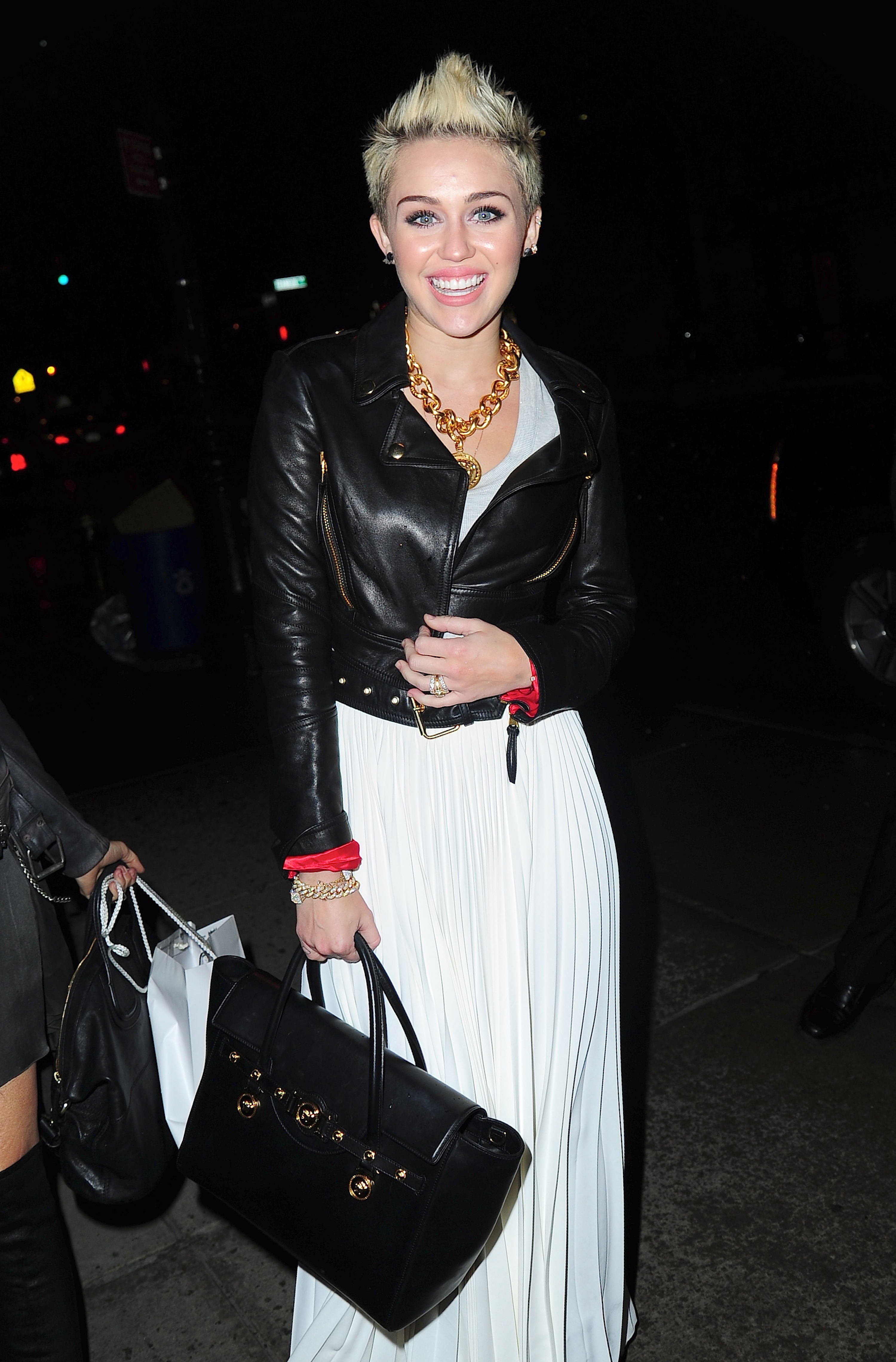 Miley Cyrus smiled on her way into the Cosmopolitan party in NYC.