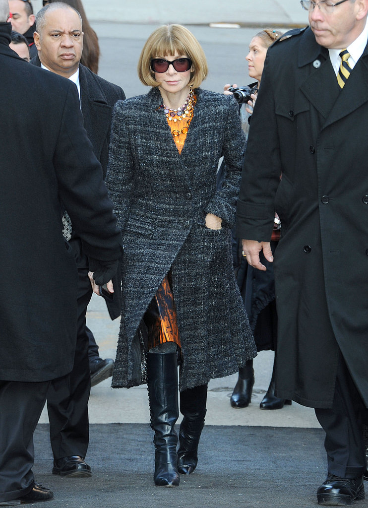 Anna Wintour arrived at Michael Kors in a printed satin sheath, long tweed coat, and black leather boots.