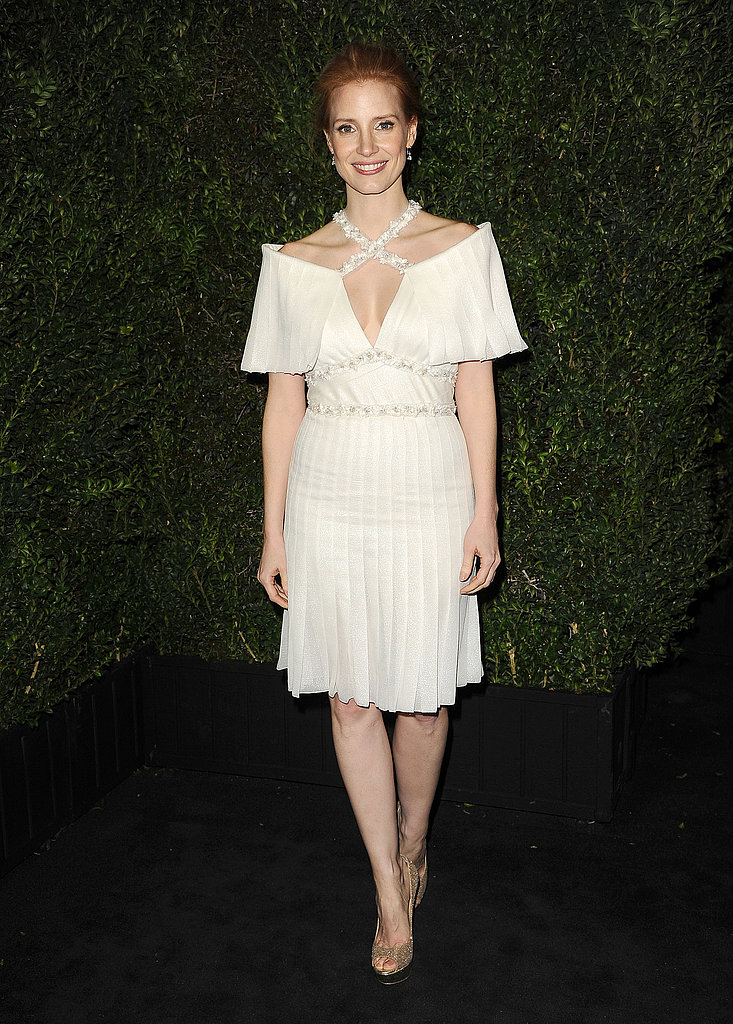 For the Chanel dinner, Jessica Chastain chose a white Chanel silk-pleated dress, complete with a crisscross jewel-encrusted neckline, from the Haute Couture Spring '13 collection.