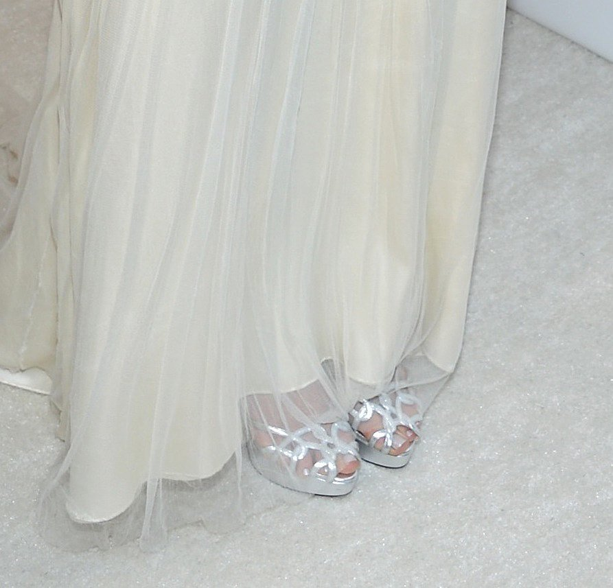 Emmy Rossum completed her ivory dress with a pair of strappy silver sandals at Elton John's viewing bash.