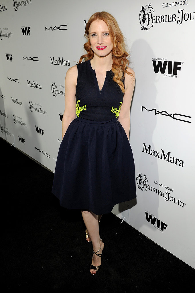 Looking lovely in a full-skirt navy Preen dress and metallic Jimmy Choo sandals, Jessica Chastain was ready to celebrate at the Women in Film party in LA.