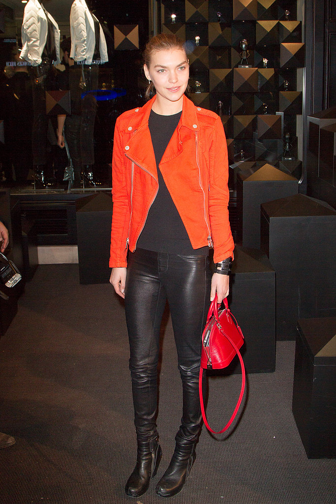 At Karl Lagerfeld's store opening in Paris, model Arizona Muse stood out from the crowd in an orange biker jacket and a mini red bag.