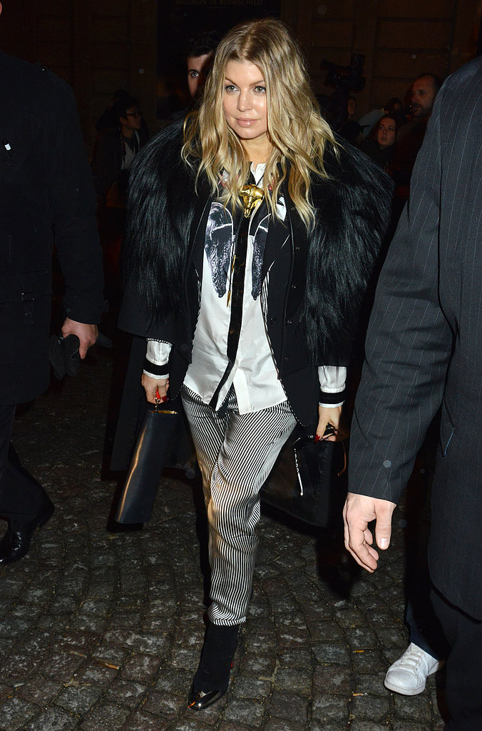 Fergie paired striped silk pants with a voluminous fur coat and leather ankle boots on her way to the Gareth Pugh show during PFW.