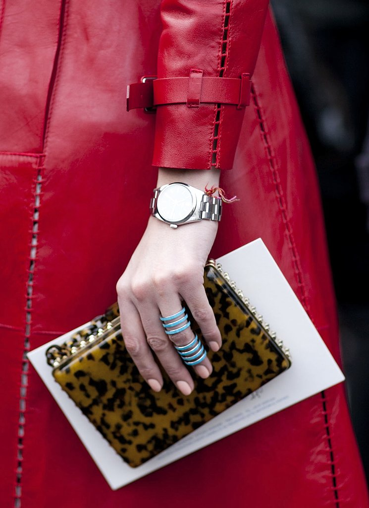 A printed clutch and turquoise Repossi ring popped against a red leather coat.