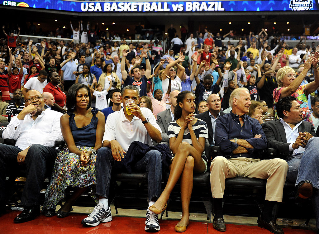 The president drank a beer while enjoying a game with his family and Vice President Joe Biden.