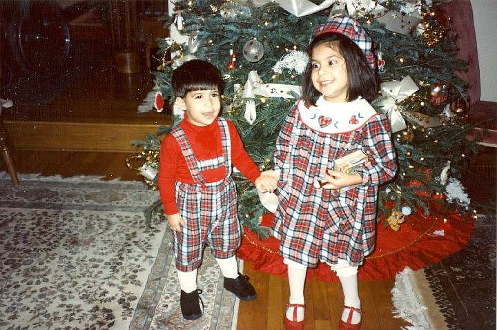 """""""My mom was really into dressing me and my sister (who is pictured as my partner in plaid) in matching outfits when we were both too young to dress ourselves. But I see what she was getting at: my plaid capri-length overalls (lederhosen?), thick red turtleneck, white socks, and black shoes were the perfect complements to our holiday decor. After all, when was the last time that you could boast not only matching your sister but also the Christmas tree skirt?"""" — Robert Khederian, editorial assistant, POPSUGAR Fashion"""