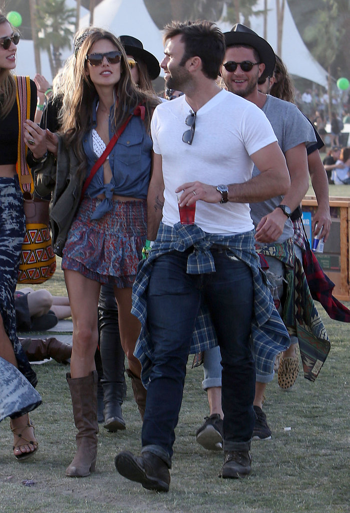 Alessandra Ambrosio exuded a modern cowgirl look in a denim button-down, a crochet bikini top, a tiered printed miniskirt, and cowboy boots.