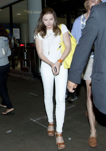 Chloë Moretz arrived at LAX airport wearing all white — including J Brand leather pants — with pops of color via a yellow bag, an orange wraparound watch, and tan platform sandals.