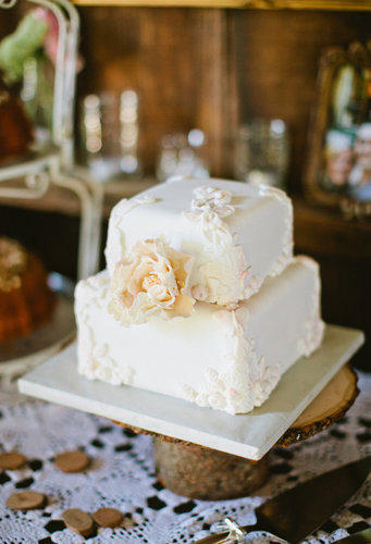 At only two layers high, this pretty, white, floral-covered cake makes a big impact.  Photo by Sarah Layne Photography via 100 Layer Cake